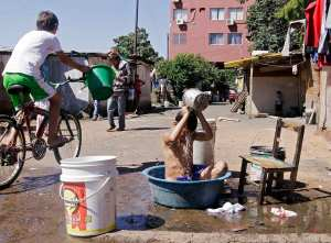 A boy bathes in a laundry basin in the Chacarita slum of Asuncion